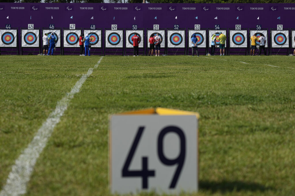 Team members check their target after a session of the men's individual recurve-open ranking round of the archery event at the Tokyo 2020 Paralympic Games, Friday, Aug. 27, 2021, in Tokyo, Japan.
