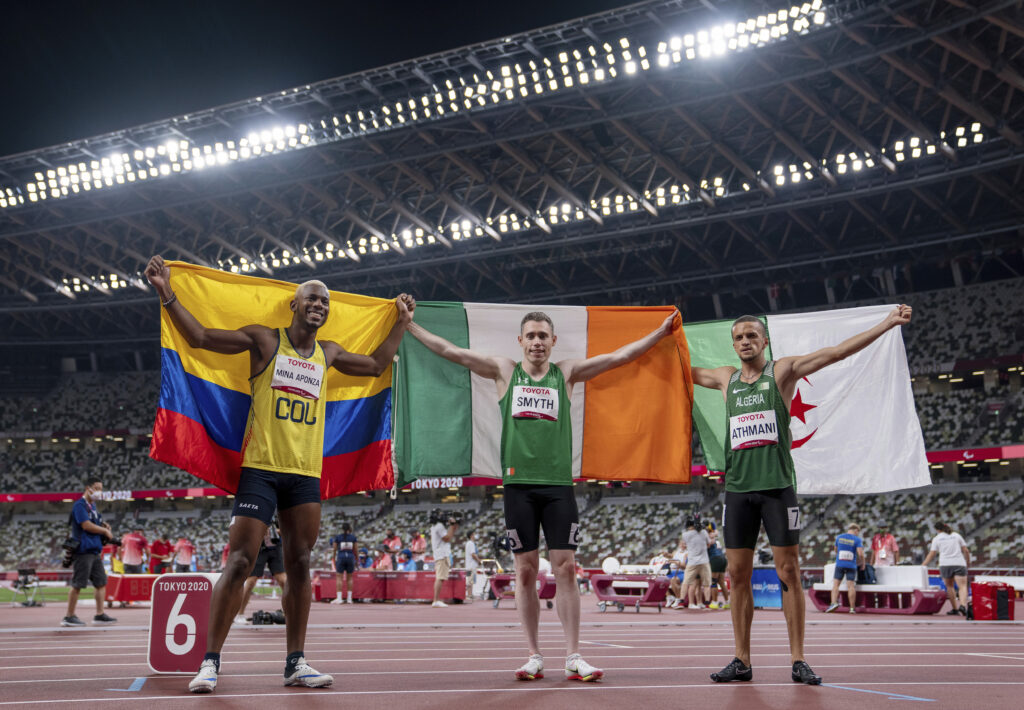 Jean Carlos Mina Aponza of Colombia (bronze medal), Jason Smyth of Ireland (gold medal) and Skander Djamil Athmani of Algeria (silver medal) celebrate their medals in the men's 100-meter T13 final at the Olympic Stadium during the Tokyo 2020 Paralympic Games in Tokyo, Japan, Sunday, Aug. 29, 2021.