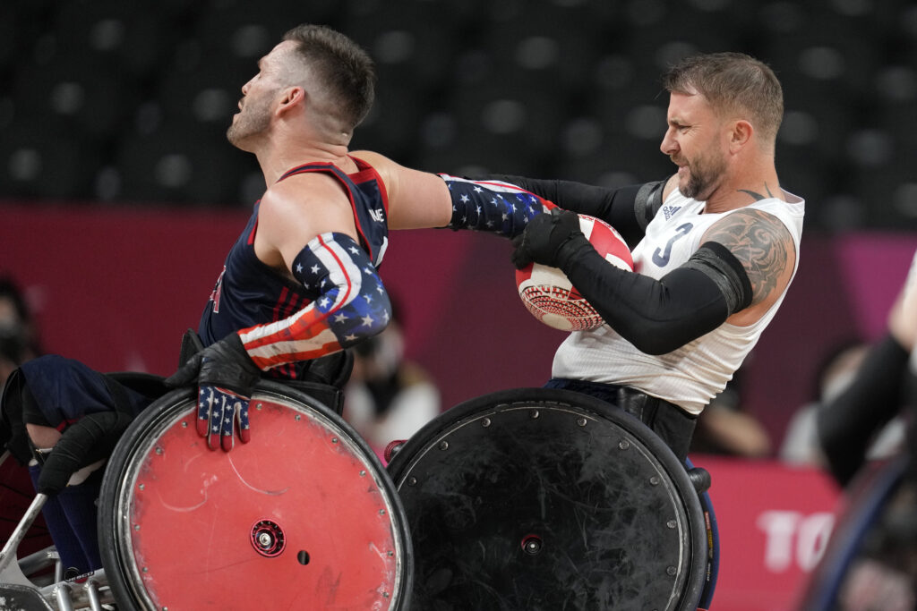 Britain's Stuart Robinson, right, holds the ball against Joshua Wheeler of the United States during the wheelchair rugby gold-medal match at the Tokyo 2020 Paralympic Games, Sunday, Aug. 29, 2021, in Tokyo, Japan.