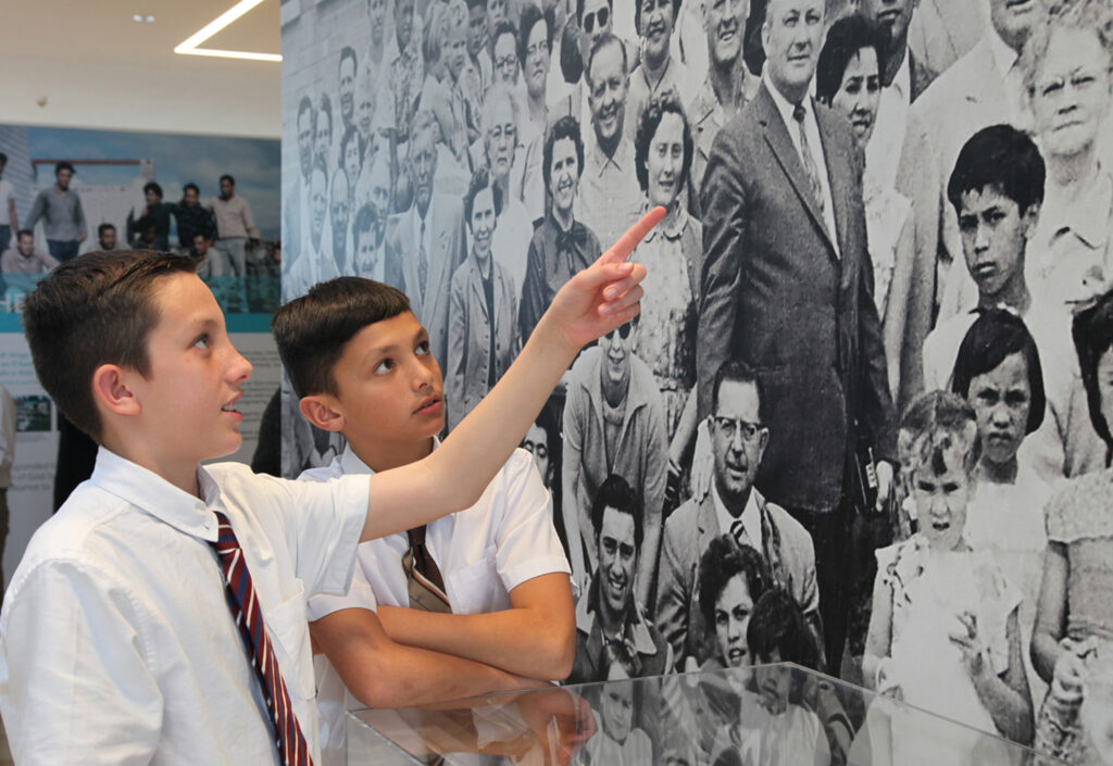 Eli and Dallin Elkington from the Hamilton, New Zealand, area, point out their great-uncle David Elkington, who served as a labor missionary, in a photo at the new exhibit at the Matthew Cowley Pacific Church History Center in Temple View, New Zealand.