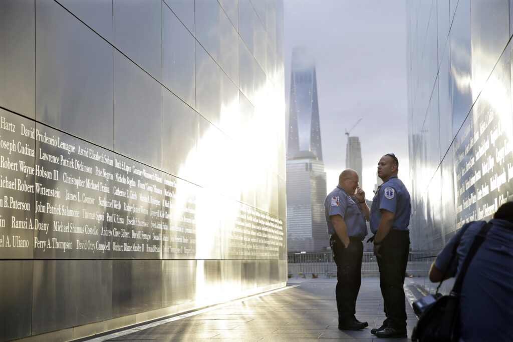 """20150911 Two Emergency Medical Technicians pause to look at the names on the """"Empty Sky"""" memorial to New Jersey's victims of the Sept. 11, 2001 terrorist attacks early Friday, Sept. 11, 2015, in Jersey City, N.J. Victims' relatives began marking the 14th anniversary of Sept. 11 in a subdued gathering Friday at ground zero, with a moment of silence and somber reading of names."""