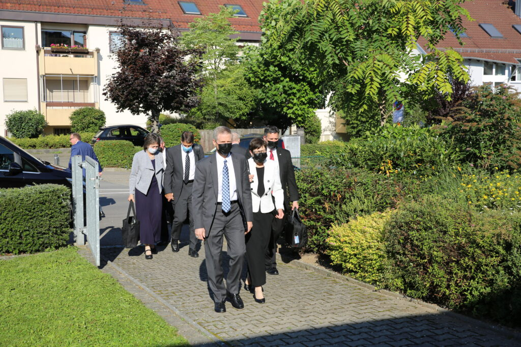 Elder David A. Bednar of the Quorum of the Twelve Apostles and his wife, Sister Susan Bednar, arrive at the Stuttgart Germany Stake center on Sept. 5, 2021, for a special stake conference broadcast to the members of the Munich, Germany, coordinating council. Elder Carl B. Cook and Sister Lynette Cook walk behind.