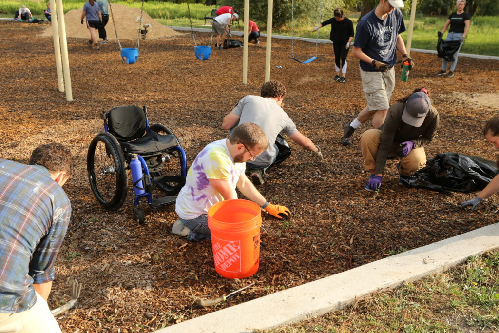 Members of the Westminster YSA Ward remove weeds from a playground in Modesto Park in South Salt Lake, Utah, as part of a JustServe and 9/11 Day service project, on Sept. 11, 2021.