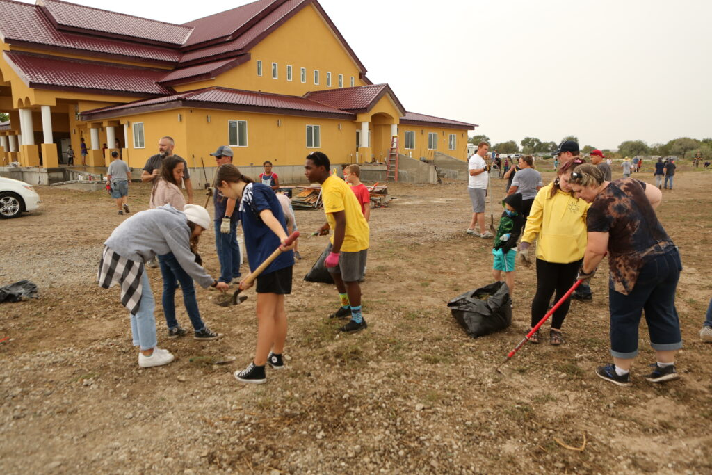 Community members clean the grounds of the Wat Lao Salt Lake Buddharam. Multi-stake members and civic volunteers brought in heavy equipment to level the parking lot, and clean away the weeds in preparation for future paving.