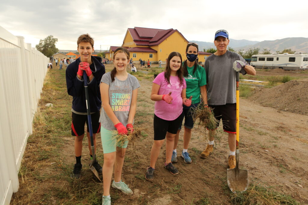 The Kirby family of the Magna Utah East Stake clean the grounds of the Wat Lao Salt Lake Buddharam. Multi-stake members and civic volunteers brought in heavy equipment to level the parking lot, and clean away the weeds in preparation for future paving.