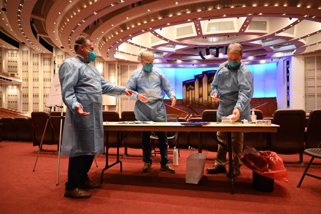 Health care workers prepare to administer COVID-19 tests on members of the Tabernacle Choir and members of the media on Tuesday, Sept. 21, 2021, in the Conference Center in Salt Lake City, Utah, leading up to the Latter-day Saint music group's first in-person rehearsal since the beginning of the pandemic.