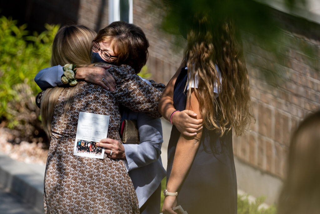 Darla Davies, widow of Elder Dean M. Davies, second from left, receives an embrace after the funeral for Elder Davies in North Salt Lake, Utah, on Saturday, Sept. 4, 2021.