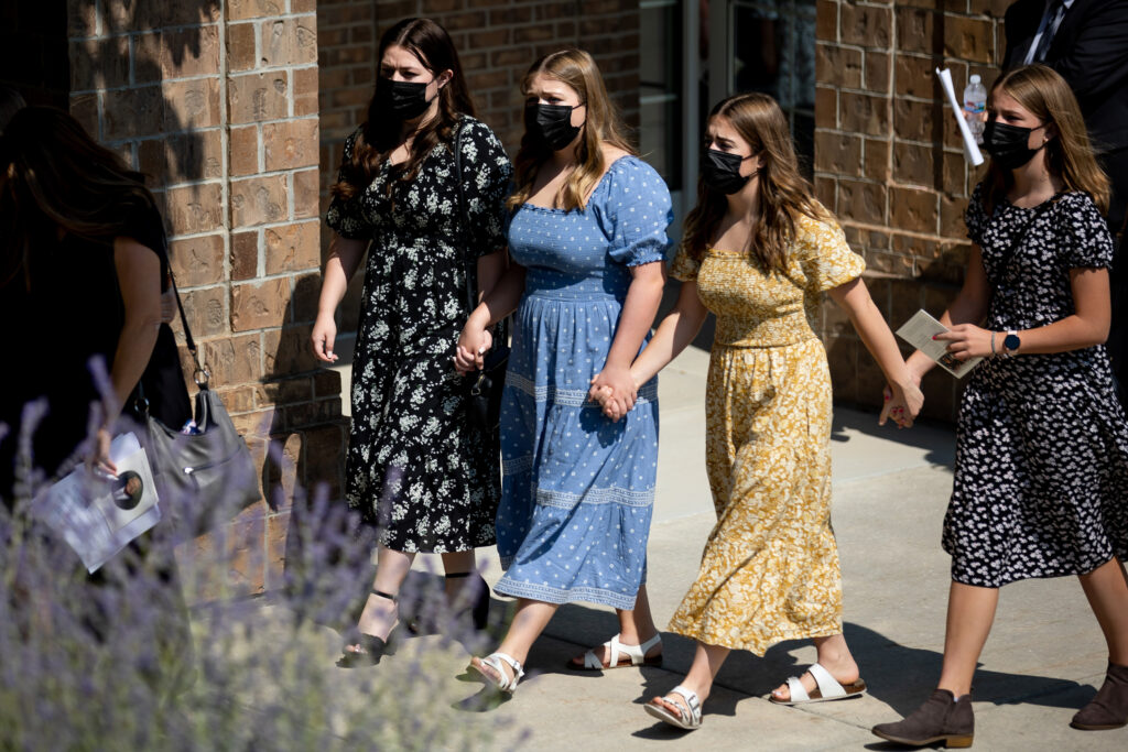 Women walk hand-in-hand as the casket is brought to a hearse after the funeral for Elder Dean M. Davies in North Salt Lake, Utah, on Saturday, Sept. 4, 2021.
