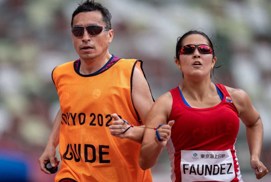 Margarita Faundez of Chile and guide Francisco Segovia race in the women's athletics 1,500-meter T11 round 1 heat 1 at the Tokyo 2020 Paralympic Games in Tokyo Sunday, Aug. 29, 2021.