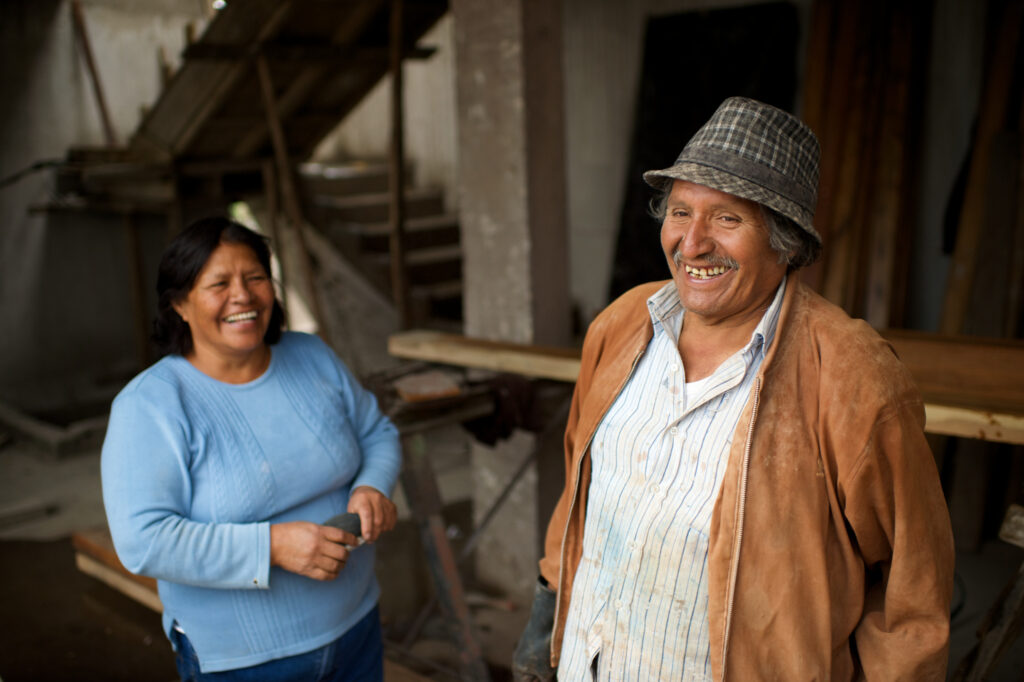 A couple from Ecuador laugh and stand in a workshop. The emotional resilience materials are currently available in English and many additional languages, including Spanish, Portuguese, French and Russian.