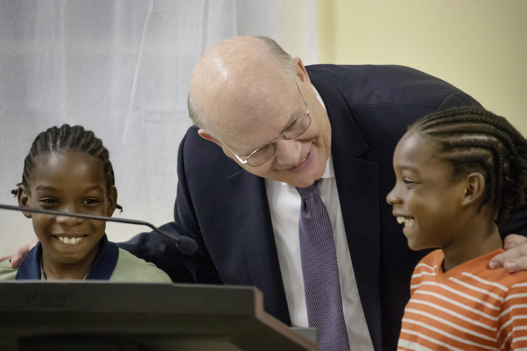 Elder Dale G. Renlund chats with two boys at the pulpit during a meeting with their congregation in Dominica during a visit to the Caribbean Area on Feb. 16, 2020.