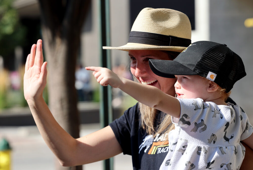 Meleah Ferguson holds daughter Ella Ferguson while waving during the Days of '47 Parade in Salt Lake City on Friday, July 23, 2021.