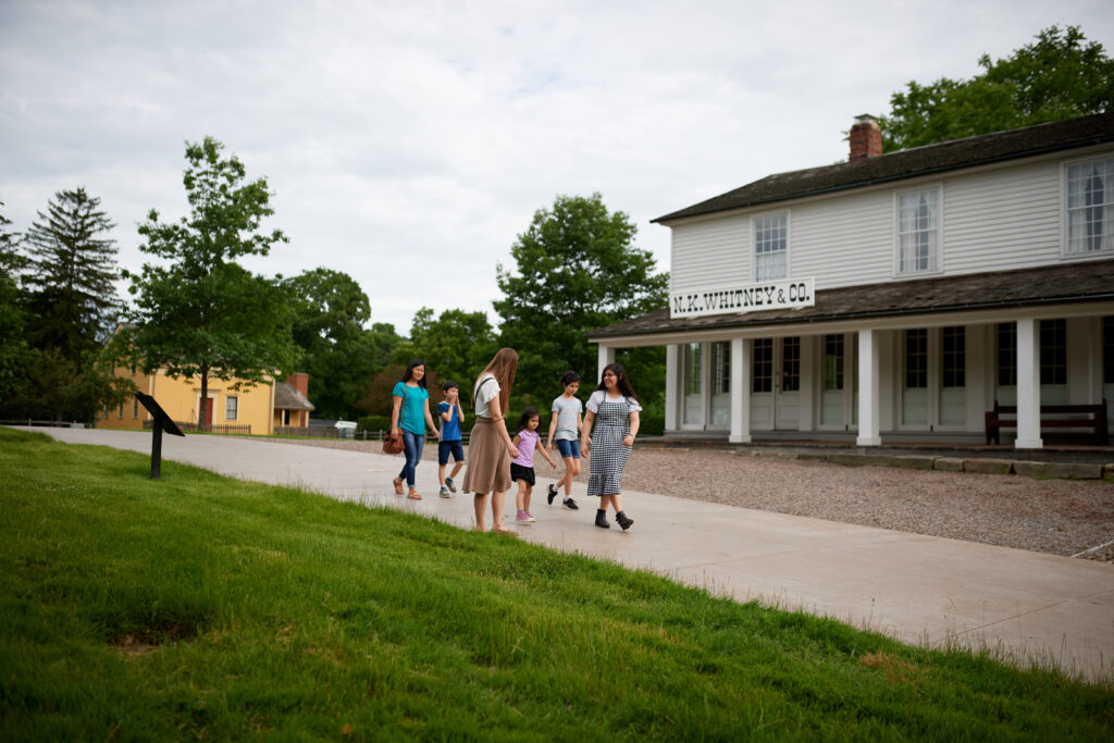 A family walks in front of the Newel K. Whitney Store in Historic Kirtland in Kirtland, Ohio, in June 2019. Joseph Smith lived here for a time and established the School of the Prophets in one of the upper rooms.
