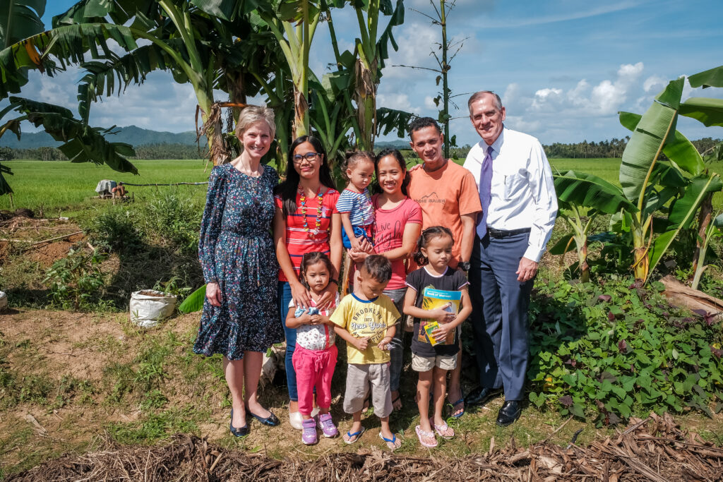 Sister Jean B. Bingham, left, and Elder Steven R. Bangerter pose for a photo with the Batiles family near their garden in Catarman, Philippines, on Feb. 3, 2020.Sister Bingham visited the area to learn of a new stake pilot program focused on malnutrition.