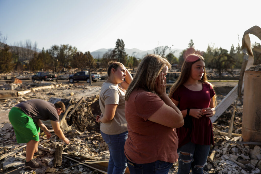 Misty Pantle and her children, Tanner, 15, Tatum, 16, and Reese, 14, left to right, make the first visit to the burned remnants of the home they and Pantle's sister, Tammy Johnson, not pictured, shared in Talent, Ore., on Saturday, Sept. 19, 2020. Their home was one of more than 2,300 residences destroyed when the Almeda Fire swept through the towns of Talent and Phoenix in southern Oregon.