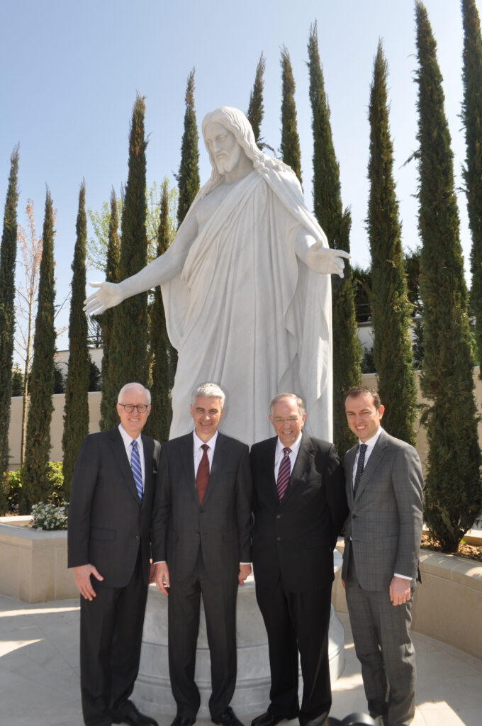 LDS Church leaders spoke for a French photographer in front of the Christus statue in the courtyard of the Paris France Temple during the temple's media day, April 7, 2017. From left, Elder Larry Y. Wilson of the Quorum of the Seventy and executive director of the Church's Temple Department; Bishop Gérald Caussé, Presiding Bishop; Elder Neil L. Andersen of the Quorum of the Twelve Apostles; and Elder Mattieu Bennasar, an Area Seventy from France who is chairman of the open house and dedication committee for the Paris temple.