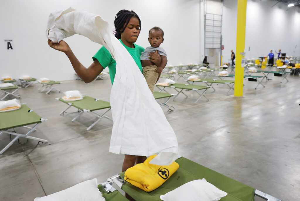 Refugee Jouseline Melayer, from Chile, holds her baby Jayden as she folds bed linens at the Family Transfer Center in Houston on Monday, June 7, 2021. The center provides a temporary respite for families who have been cleared at the United States border and need short-term shelter and food. The creation of the Family Transfer Center is the result of a collaboration among The Church of Jesus Christ of Latter-day Saints, Catholic Charities, the National Association of Christian Churches, YMCA International Services, Texas Adventist Community Services, Houston Responds and the Houston Food Bank.