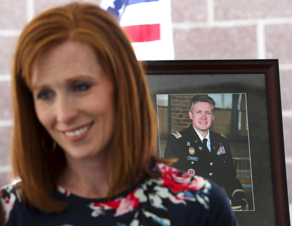 Jennie Taylor talks to guests about her husband, Maj. Brent Taylor, pictured at back, who was killed in Afghanistan in 2018, during a dedication ceremony for the newly renamed Major Brent Taylor Vet Center Outstation in North Ogden on Monday, June 10, 2019.