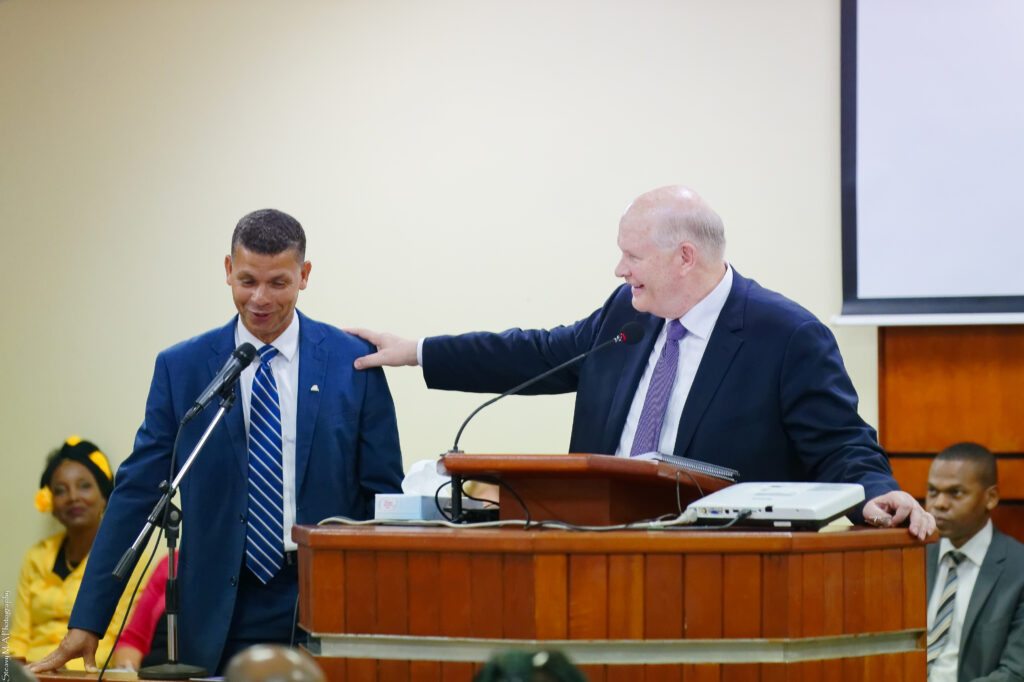 Elder Dale G. Renlund places his hand on the should of a member at the pulpit during a meeting with Latter-day Saints in Guadeloupe on Feb. 17, 2020. The apostle's visit to the island came as part of the Caribbean Area annual review.