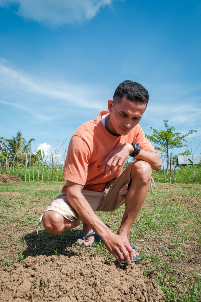 Franco Batiles crouches over a mound of dirt in his garden in Catarman, Philippines,on Feb. 3, 2020, to show visitors the new sprouts popping up after his garden was destroyed by Typhoon Tisoy in December 2019.