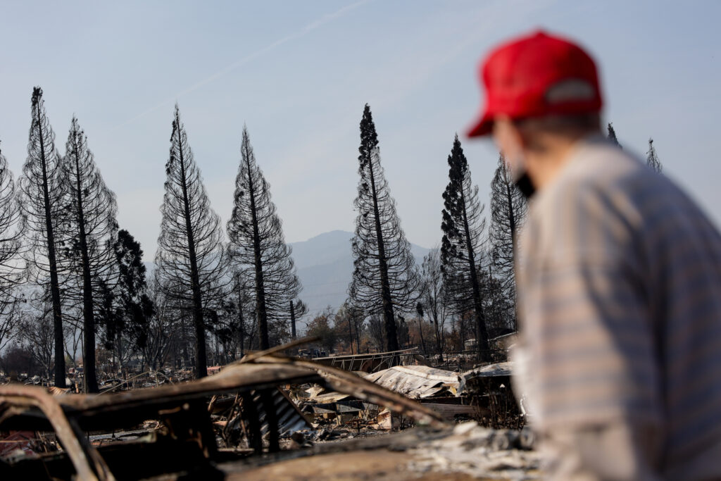 Blackened trees stand as a backdrop as Leonard Sander searches through the burned remnants of his home in the Medford Estates neighborhood of Medford, Oregon, on Monday, Sept. 21, 2020. Sander's home was one of at least 2,357 homes burned in the Almeda Fire.