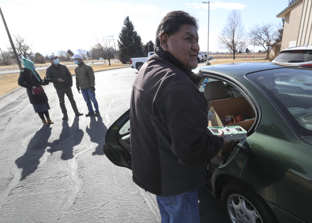 Leon Allen Anthony, a Navajo artist from Pocatello, picks up a food box from volunteers from The Church of Jesus Christ of Latter-day Saints during a food giveaway at the chapel along U.S. 91 between West Tyhee and West Reservation roads in Fort Hall, Idaho, on Monday, Feb. 1, 2021. The event was part of the Farmers to Families Food Box Program and is part of the USDA's Families First Coronavirus Response Act.