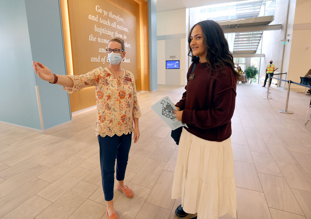 Sister Nina Smith directs Sister Tayah Langi as she moves through the check-in process at the Provo Missionary Training Center in Provo on Wednesday, Aug. 18, 2021.
