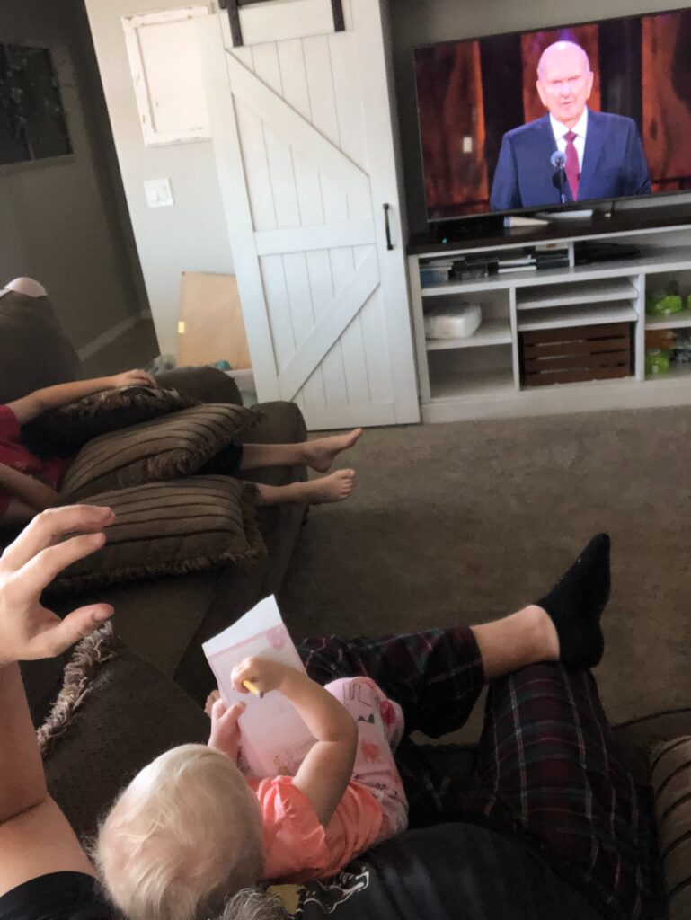 """Clay Cook, of the Lake Pleasant Ward, Peoria Arizona North Stake, holds Kinder Cook, who is """"taking notes"""" while listening to President Russell M. Nelson during the Sunday morning session of the 190th Semiannual General Conference of The Church of Jesus Christ of Latter-day Saints on Oct. 4, 2020."""