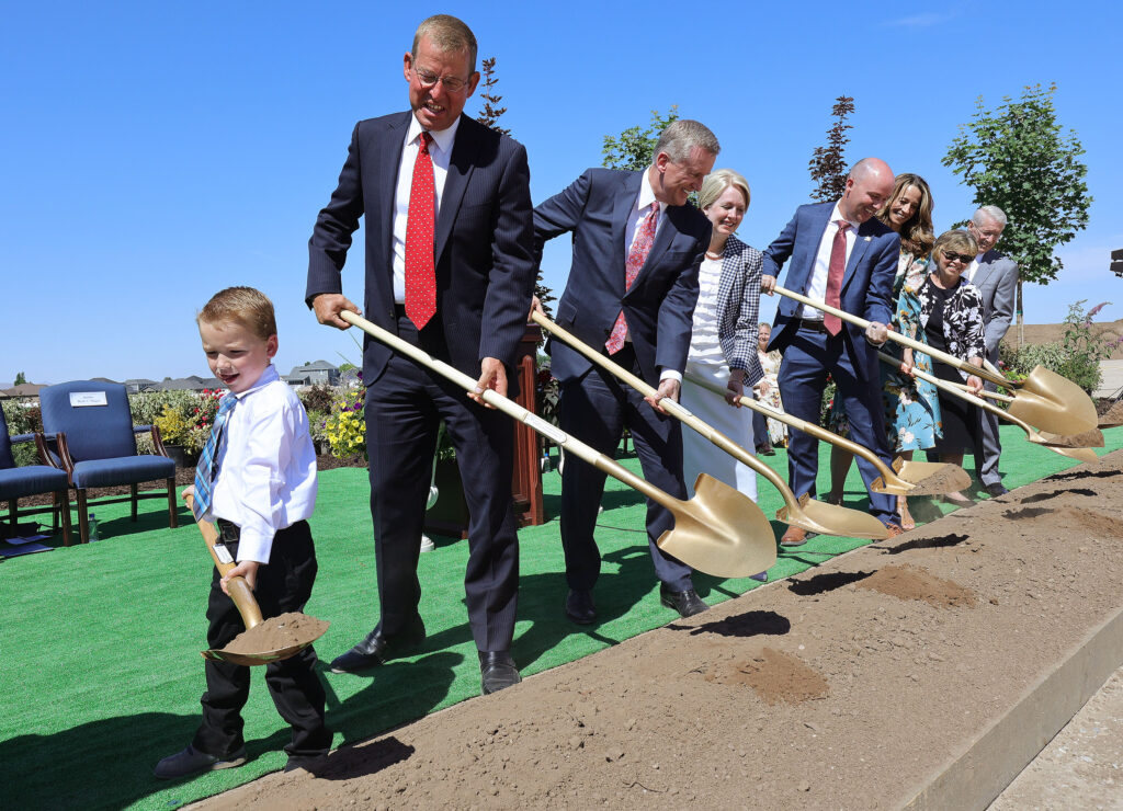 Emmett Thayne, 5, grandson to Mark S. Thayne, joins Elder Kevin R. Duncan, third from left, in turning over soil during groundbreaking for the Syracuse Utah Temple of The Church of Jesus Christ of Latter-day Saints in Syracuse on Saturday, June 12, 2021.