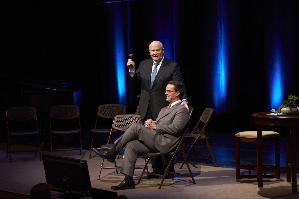 Elder Dale G. Renlund, standing, displays a reflex hammer that he will use on Elder Shayne M. Bowen in a demonstration at the 2020 Temple and Family History Leadership Instruction meeting Thursday, Feb., 27, 2020, at the Conference Center Theater in Salt Lake City, Utah.