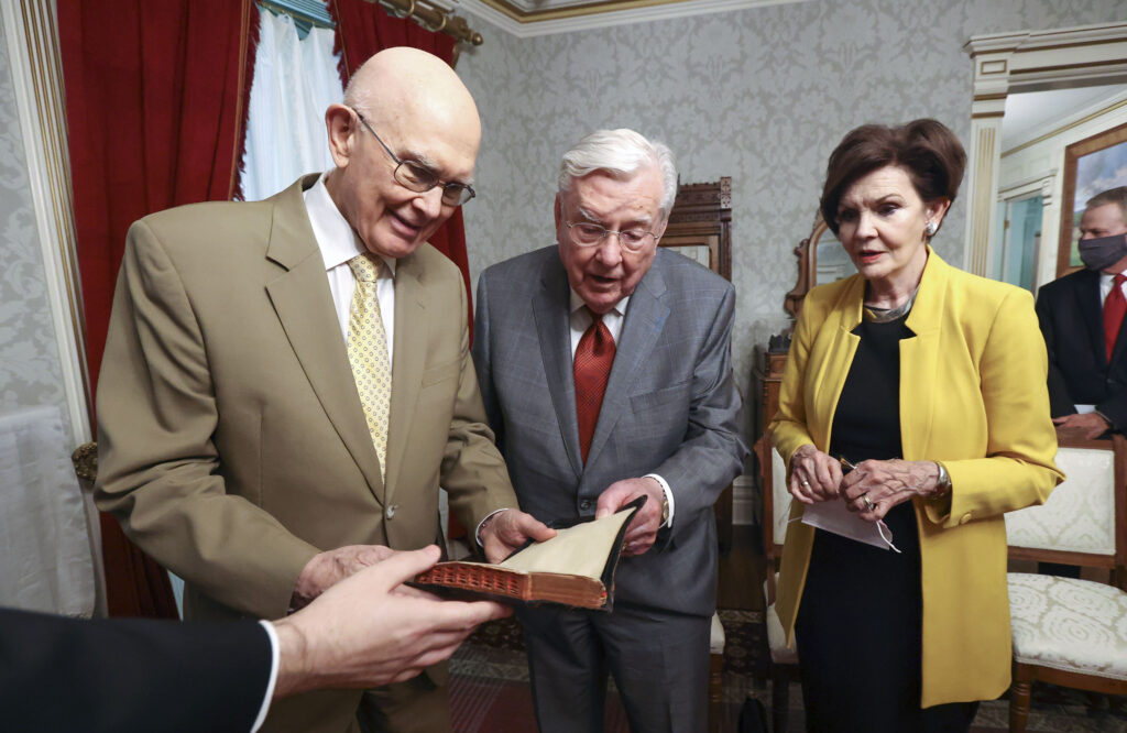 President Dallin H. Oaks, first counselor in the First Presidency, President M. Russell Ballard, acting president of the Quorum of the Twelve Apostles, and Sister Kristen M. Oaks look through Joseph F. Smith's bible while touring Smith's bedroom in the Beehive House in Salt Lake City on Friday, Sept. 24, 2021. President Ballard and Sister Oaks are descendants of Joseph F. Smith.