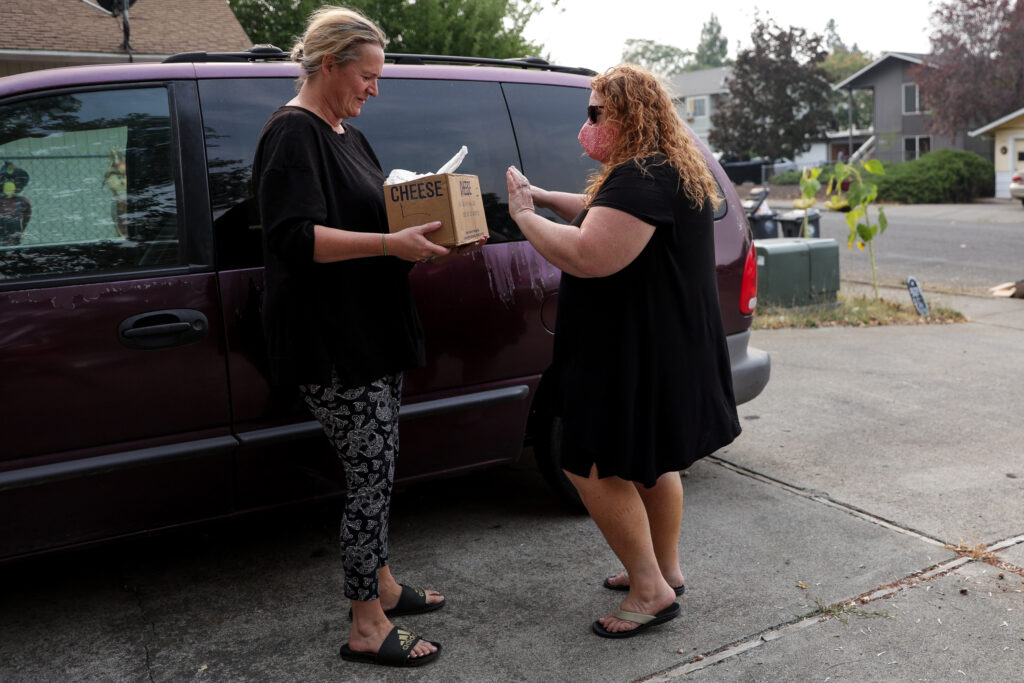 Bear Creek Ward Relief Society President Deni Goodwin, right, hands off part of a food order to Kimberly LaPointe at her home in Phoenix, Oregon, on Monday, Sept. 21, 2020.