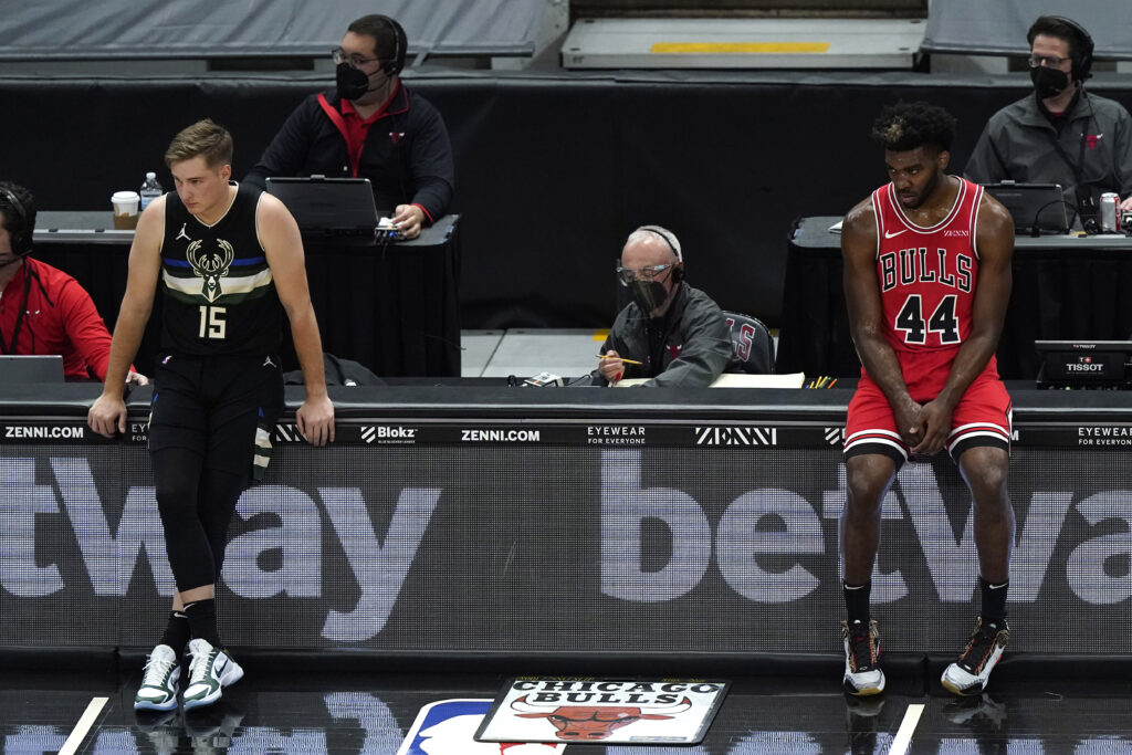 Milwaukee Bucks guard Sam Merrill, left, and Chicago Bulls forward Patrick Williams watch teammates during the first half of an NBA basketball game in Chicago, Sunday, May 16, 2021.