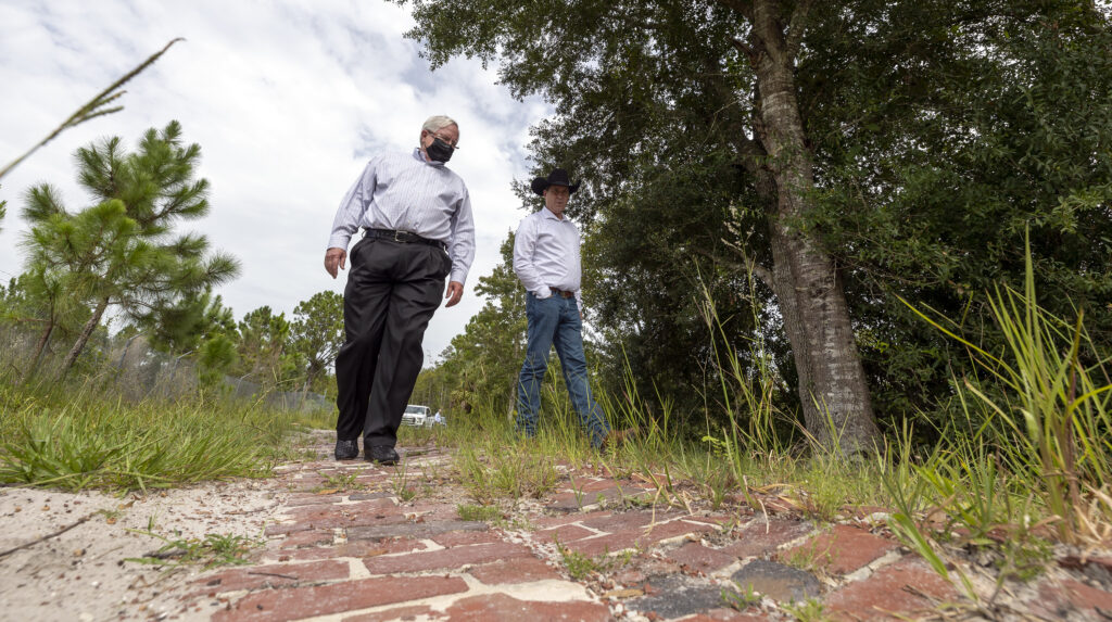 Don Whyte, vice president of planning, and Clint Richardson, general manager of Deseret Ranches in St. Cloud, Florida, walk on an old brick roadway that is on the property on Monday, Aug. 23, 2021.