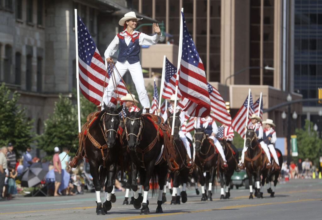 A woman straddles two horses while participating in the Days of '47 Parade in Salt Lake City on Friday, July 23, 2021.