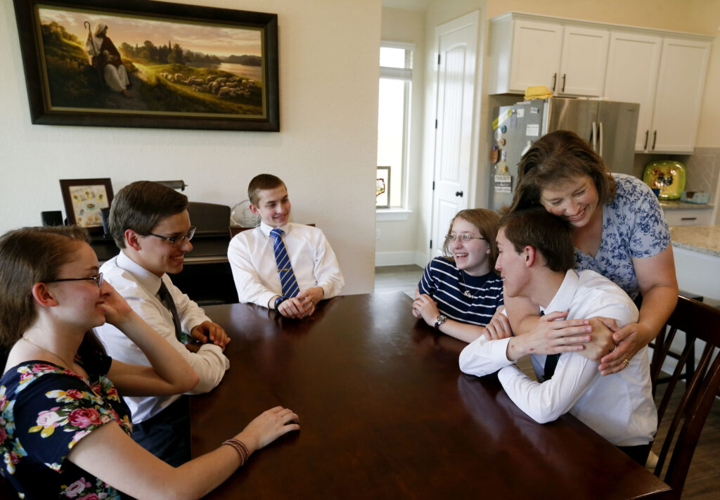 Cathryn, left, Joshua, Jonathan and Nataleigh laugh as their mother, Nichole Faylor, hugs Joseph as the Faylor family chats at their San Antonio, Texas, home on Sunday, June 20, 2021.
