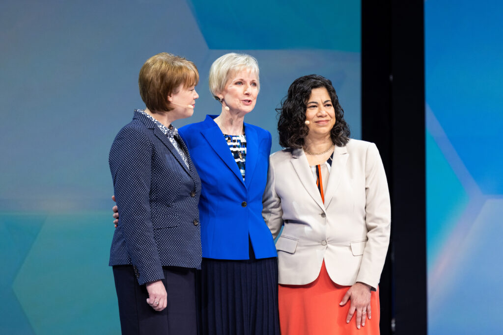 Relief Society General President Jean B. Bingham, center, stands with her counselors, Sister Sharon Eubank, left, and Sister Reyna Isabel Aburto, right, on stage in the Marriott Center in Provo, Utah, during BYU Women's Conference on April 29, 2021.