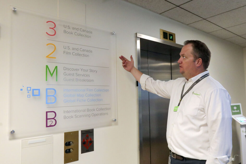 Lynn Turner, assistant director of The Church of Jesus Christ of Latter-day Saints' Family History Library, shows new signs that reflect changes in what is located on each floor after a recent remodel at the library in Salt Lake City on Tuesday, June 29, 2021.