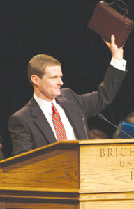 Elder David A. Bednar raises his scriptures in what has become tradition at BYU-Idaho devotional assemblies.