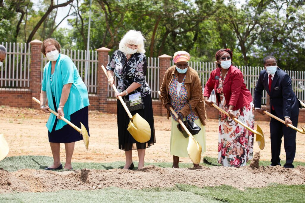 Latter-day Saint leaders turn the soil together at the groundbreaking of the Zimbabwe Harare Temple on Saturday, Dec. 12, 2020.