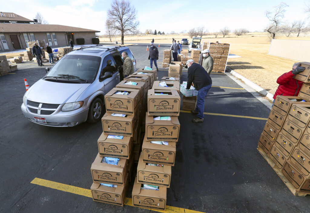 Volunteers from The Church of Jesus Christ of Latter-day Saints pack USDA food boxes into waiting vehicles during a giveaway at the chapel along U.S. 91 between West Tyhee and West Reservation roads in Fort Hall, Idaho, on Monday, Feb. 1, 2021. The event is part of the Farmers to Families Food Box Program and is part of the USDA's Families First Coronavirus Response Act.
