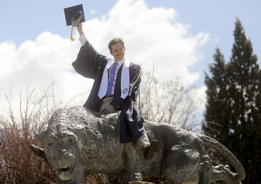Jack Hoen poses on a cougar statue as his loved ones take photos of him outside of LaVell Edwards Stadium after BYU's virtual graduation ceremony in Provo on Thursday, April 22, 2021. Due to COVID-19, the graduation ceremony was broadcast from the Marriott Center and held virtually.
