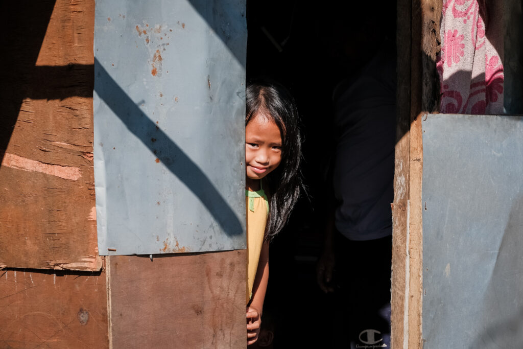 A young girl pokes her head out of her front door in Catarman, Philippines, on Feb. 3, 2020.Sister Jean B. Bingham visited families in the area to learn about a stake pilot program focused on addressing malnutrition in the area.