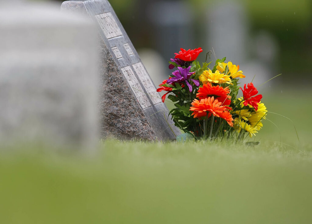 Flowers are next to a headstone at the Salt Lake City Cemetery on Sunday, May 23, 2010.