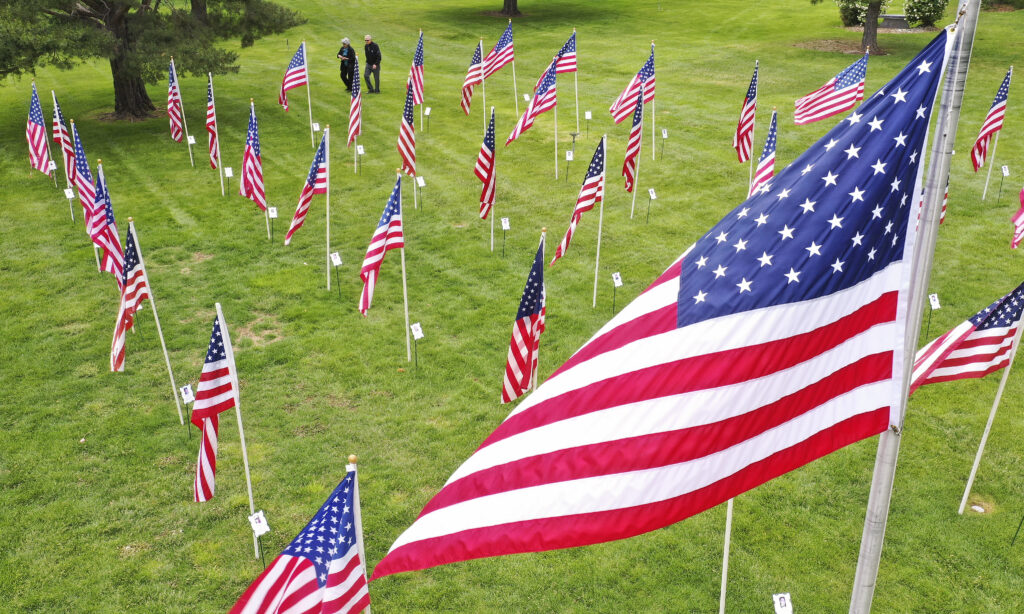 A couple walks through the Flags of Honor at Memorial Mountain View Cemetery in Cottonwood Heights, Utah, on Sunday, May 24, 2020. The flags honored soldiers who had died since 9/11.