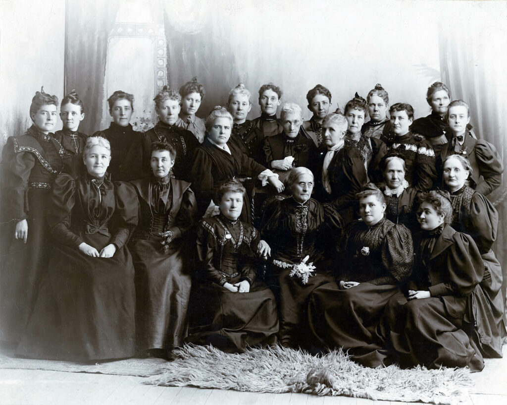 Through her support of women's suffrage, Emmeline B. Wells (standing near center of photograph, with white scarf) won the respect of national suffrage leaders, including Susan B. Anthony (front row, third from right). Anthony and Wells maintained a lifelong friendship.