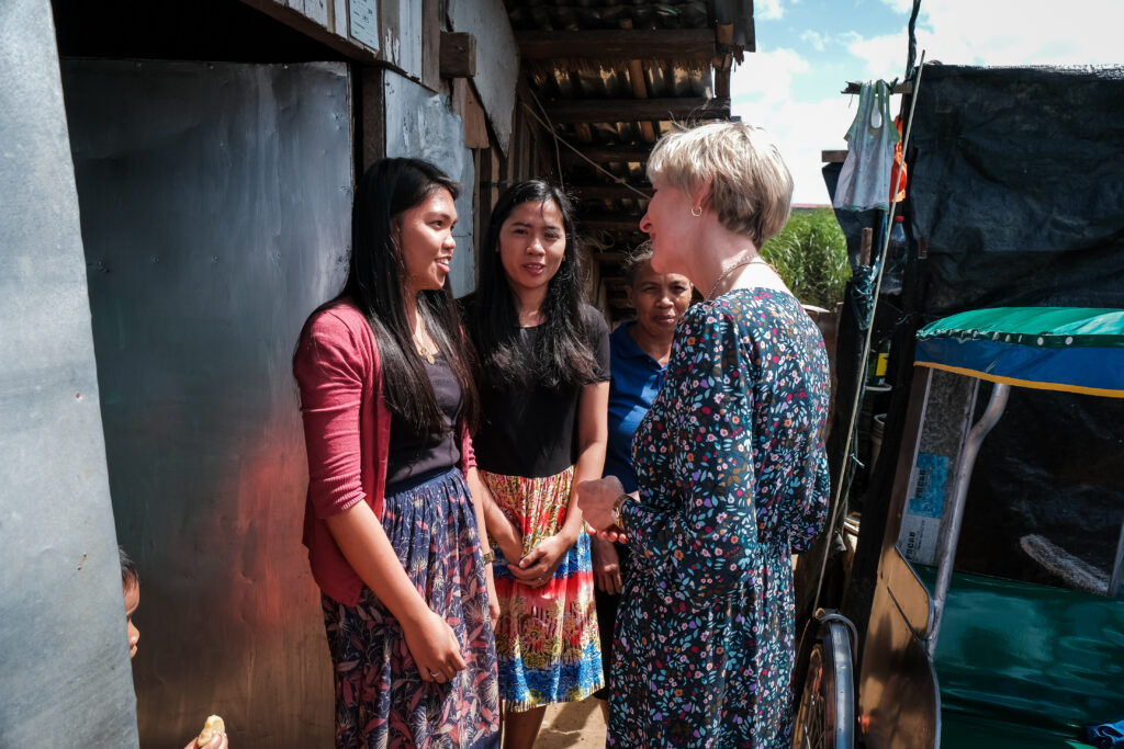 President Jean B. Bingham speaks with Charlene Lagrimas, left, and Maribel Chu, center, outside of the home of a family they minister to as part of a stake pilot program focused on malnutrition in Catarman, Philippines, on Feb. 3, 2020.