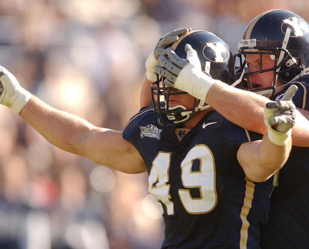 Brigham Young's Brady Poppinga is mobbed by teammate Paul Walkenhorst after one of his sacks Nov. 2, 2002.