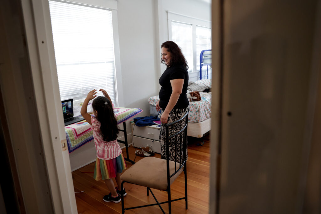Lucy Navas watches as her daughter, Allison Contreras Navas, 6, dances during an online class in the apartment they've moved into in Medford, Oregon, on Tuesday, Sept. 22, 2020. Navas, her two children and her parents lived together in a mobile home that burned to the ground in the Almeda Fire. Now they are sharing a two-bedroom apartment provided by a fellow member of The Church of Jesus Christ of Latter-day Saints.