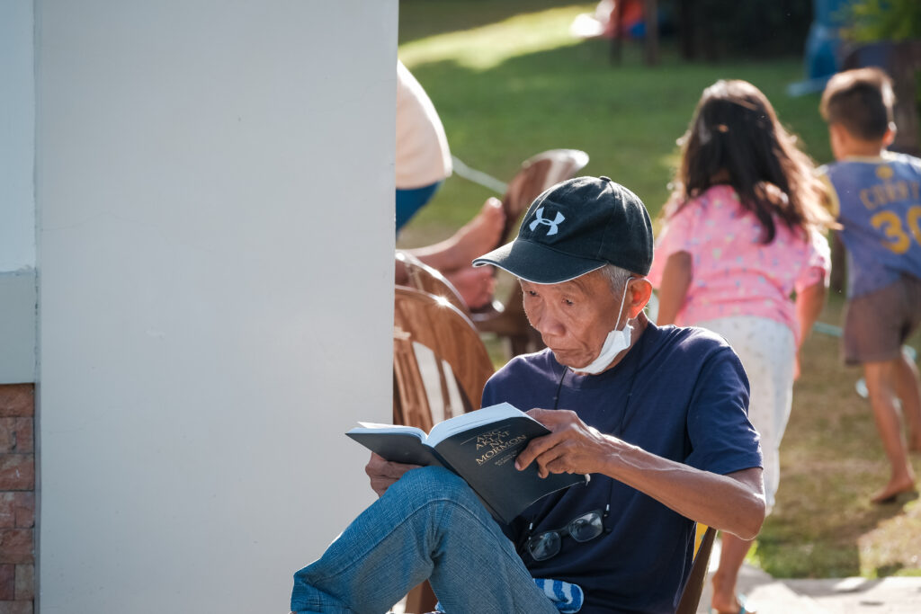 An evacuee from Lemery City reads a copy of the Book of Mormon outside of the Batangas Philippines Stake Center on Feb. 6, 2020. Evacuees have been staying at the Church meetinghouse for three weeks.